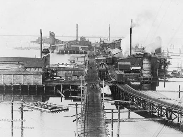 A western view of the 14th Street dock, built by the Everett Land Company, lined with several small mills and a railroad spur to service them, circa 1916.    Photo courtesy of Everett Public Library.