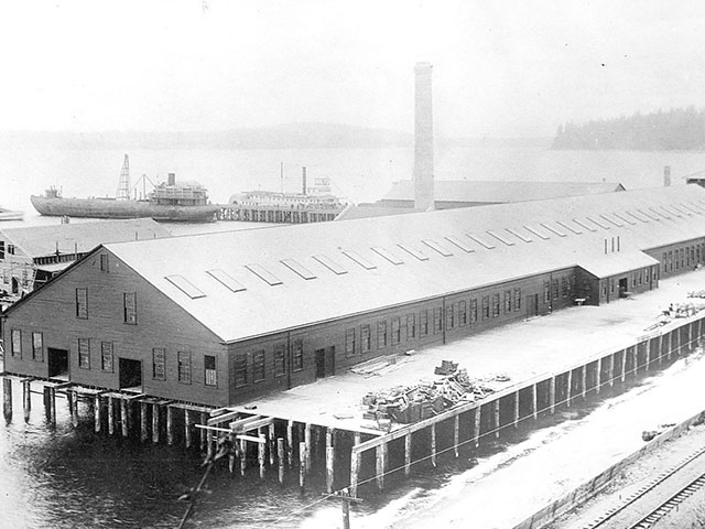 A 1892 view of the Puget Sound Wire Nail and Steel Company in the foreground, as the Charles W. Wetmore whaleback is docked.  Photo courtesy of Everett Public Library, photographers R. King and D. W. Baskerville.